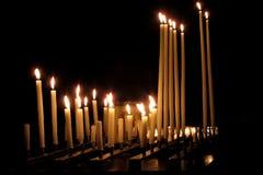 Bougies religieuses brûlant dans une église foncée Image libre de droits