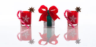 Bougies rouges, bougeoirs avec les flocons de neige en cristal, cannes à sucre et étoiles d'anis et un boîte-cadeau, d'isolement  Image stock