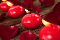 Bougies rouges de cire entourées avec des pétales de rose Photo stock