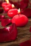 Bougies rouges de cire entourées avec des pétales de rose Images libres de droits