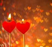 Bougies rouges de coeurs sur le bokeh chaud de coeurs comme fond Images libres de droits