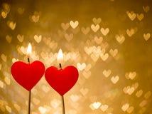 Bougies rouges de coeurs sur le bokeh d'or de coeurs comme fond Photographie stock