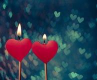 Bougies rouges de coeurs sur le bokeh de coeurs de vintage comme fond Image libre de droits