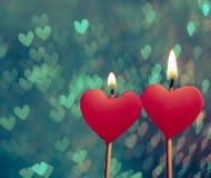 Bougies rouges de coeurs sur le bokeh de coeurs de vintage comme fond Photos libres de droits