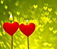 Bougies rouges de coeurs sur le bokeh jaune de coeurs comme fond Image stock