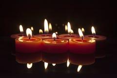 Bougies rouges et pourprées sur le fond noir Photographie stock