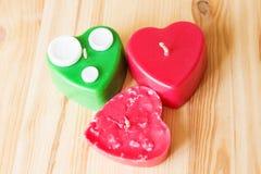 Bougies rouges et vertes découpées sur la surface en bois texturisée Images stock