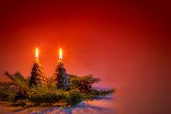 Bougies sous forme d'arbres de Noël sur un fond rouge Photo stock