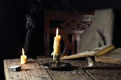 Bougies sur la table avec la montre de livre et de poche photographie stock libre de droits