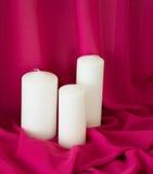 Bougies sur le fond rose de tissu de tissu de texture romantique Photo stock