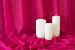 Bougies sur le fond rose de tissu de tissu de texture romantique Photographie stock