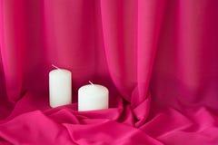 Bougies sur le fond rose de tissu de tissu de texture romantique Image libre de droits