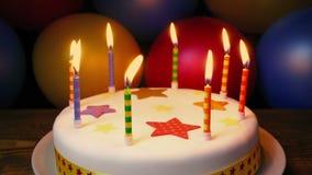 Bougies sur le gâteau d'anniversaire avec les ballons colorés banque de vidéos