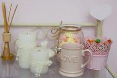 Bougies, tasse et bonbons sur la table dans le salon de beauté Images stock