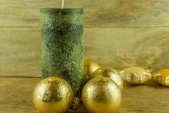 Bougies vertes avec les boules d'or de Noël sur un conseil rustique Photo libre de droits