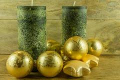 Bougies vertes avec les boules d'or de Noël sur un conseil rustique Images libres de droits