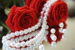 Bouguet των κόκκινων τριαντάφυλλων με τα πράσινα φύλλα, με ένα περιδέραιο των άσπρων μαργαριταριών και των διεσπαρμένων χαντρών π στοκ εικόνες