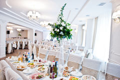 Bouguet of flowers on vase at guest table on wedding hall. Royalty Free Stock Images