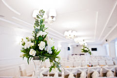 Bouguet of flowers on vase at guest table on wedding hall. Royalty Free Stock Photo