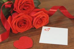 Bouguet of red roses tied with red satin ribbon, a souvenir in the for of heart of red color and a small piece of paper painted h. Some red roses in the bouguet stock photo