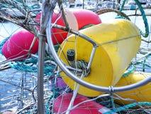 Bouies rose et jaune dans des cages en métal dans un port d'Alaska photographie stock libre de droits