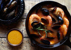 Bouillabaisse fish soup with prawns, mussels tomato, lobster. Sauce Rouille. Rustic style background. Flat lay. Royalty Free Stock Photos