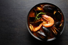 Bouillabaisse fish soup with prawns, mussels, tomato, lobster and squid. Traditional in France, Spain. Black background. Stock Photos