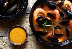 Bouillabaisse fish soup with seafood, prawns, mussels tomato, lobster. Sauce Rouille. Rustic style background. Flat lay. Stock Image
