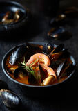 Bouillabaisse tomato fish soup with prawns, mussels, lobster and squid. Traditional in France, Spain. Black background. Royalty Free Stock Photo