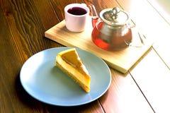 Bouilloire avec le thé de fruit et le gâteau au fromage rouges de chocolat Photo libre de droits