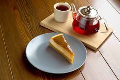 Bouilloire avec le thé de fruit et le gâteau au fromage rouges de chocolat Images stock