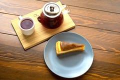 Bouilloire avec le thé de fruit et le gâteau au fromage rouges de chocolat Image stock