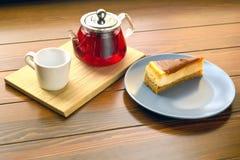 Bouilloire avec le thé de fruit et le gâteau au fromage rouges de chocolat Photos stock