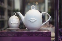 Bouilloire blanche de porcelaine avec une tasse dans la fenêtre d'une boutique de porcelaine Photographie stock