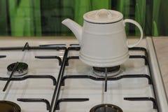 Bouilloire blanche sur une cuisinière à gaz dans la cuisine photographie stock