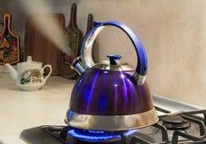 Bouilloire d'eau bouillante sur la flamme de la cuisinière à gaz image libre de droits