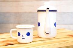 Bouilloire de bande dessinée et tasse de café avec un sourire heureux sur la table en bois Image libre de droits
