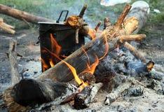 Bouilloire de touristes sur le feu de camp Photographie stock libre de droits