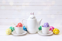 Bouilloire-lièvres avec des tasses et des oeufs de pâques sur un fond blanc Photo stock
