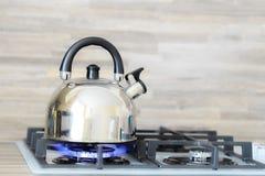 Bouilloire sur une brûlure de flamme de cuisinière à gaz ne bouillant pas photo stock