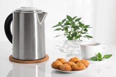 Bouilloire, tasse de thé et biscuits électriques images libres de droits