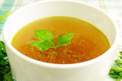 Bouillon, broth, clear soup. In a white cup with a loaf, parsley, boiled egg on the tablecloth. Close-up Stock Image