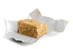 Bouillon cube. In opened paper wrapping over white background Royalty Free Stock Photos