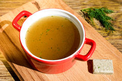 Bouillon cube. Concentrated broth, bouillon, clear soup in a cup and a bouillon cube Royalty Free Stock Photography