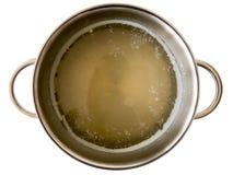 Bouillon jaune avec de la graisse blanche dans la casserole d'acier inoxydable d'isolement sur le blanc Images libres de droits