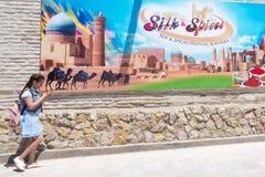 BOUKHARA, OEZBEKISTAN - MEI 25, 2018: Zijde en Kruidenfestival 2018 Schoolmeisje die met mobiele telefoon tegen de banner lopen Stock Foto's