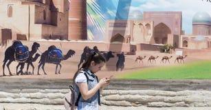BOUKHARA, OEZBEKISTAN - MEI 25, 2018: Zijde en Kruidenfestival 2018 Schoolmeisje die met mobiele telefoon tegen de banner lopen Royalty-vrije Stock Foto's