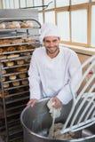 Boulanger de sourire préparant la pâte dans le mélangeur industriel images libres de droits