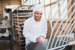 Boulanger de sourire préparant la pâte dans le mélangeur industriel image libre de droits