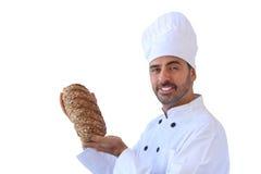 Boulanger de sourire tenant le pain de blé entier photos libres de droits